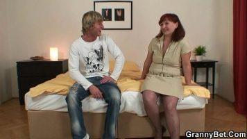 Un barbat blond si o femeie batrana roscata care se ating si incep sa se dezbrace
