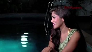 Doua tinere care servesc cate un pahar de vin la piscina se saruta senzual si incep sa se