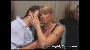 Blonda cu sanii foarte mari care isi saruta amandoi partenerii dorind sa o faca sa